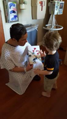 Picture of my son presenting a get-well card to me before my surgery. This would be my last visit with him before the surgery.